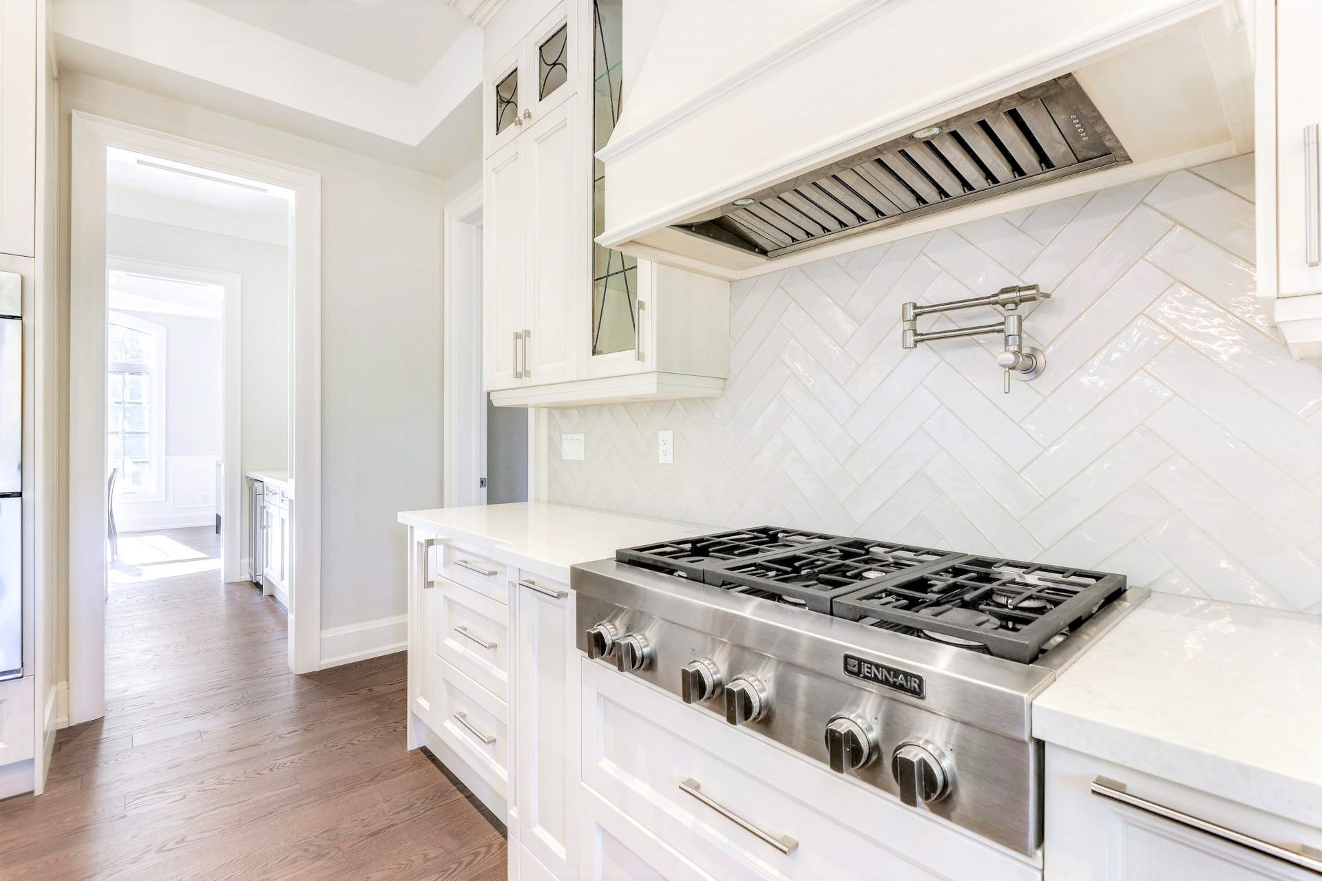 white kitchen with silver cooktop